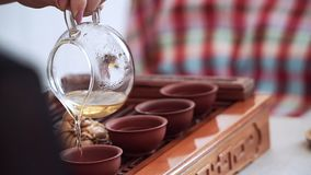 From a glass teapot poured fragrant tea into small cups on wooden table.  stock video footage