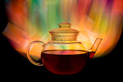 Glass teapot with red tea and fire looking background Royalty Free Stock Photo