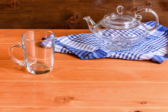 Glass teapot stands on a blue towel on a wooden background Stock Images