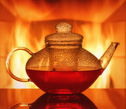 A glass teapot at the table in front of a fireplace. A teapot at the table in front of a fireplace stock images