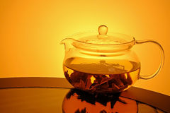 Glass teapot with tea on glass table Stock Photo