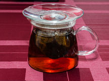 Glass teapot. Tea is ready in the glass teapot standing on a checkered cloth Royalty Free Stock Image