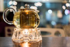 Glass Teapot with Warmer. Hot teapot with warmer on wood table Stock Image
