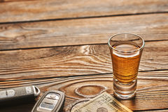 Glass of tequila or alcohol drink and car key. Drink and drive concept. Stock Images
