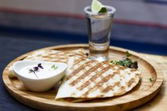 The glass of tequila with lime and portion of quesadilla on round board. The glass of tequila with lime and portion of quesadilla on round wooden Board, Mexican royalty free stock photography