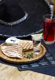 The glass of tequila with lime and portion of quesadilla with sombrero background. The glass of tequila with lime and portion of quesadilla on round wooden Board royalty free stock photo