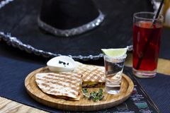 The glass of tequila with lime and portion of quesadilla on round board. The glass of tequila with lime and portion of quesadilla on round wooden Board with stock photo