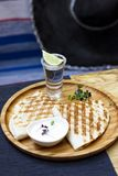 The glass of tequila with lime and portion of quesadilla on round board. The glass of tequila with lime and portion of quesadilla on round wooden Board with royalty free stock photography
