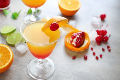 Glass of Tequila Sunrise cocktail with ingredients. On grey background Royalty Free Stock Images