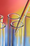 Glass test tubes. Closeup of glass test tubes and a glass pipette on a brightly colored background Royalty Free Stock Images