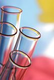 Glass test tubes. Four glass test tubes on a colorful background Stock Photos