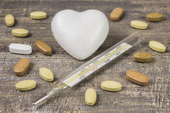 Glass thermometer, heart medications tablets the background wooden table. The view from the top Stock Images