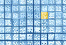Glass tile difference. Different yellow transparent glass tile in blue window wall grid background Royalty Free Stock Image