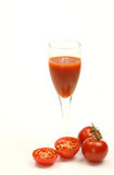 Glass of tomato juice. With whole and sliced tomatoes Stock Images