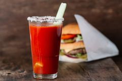 Glass of tomato juice with a celery stick. And a big burger on a wooden background stock photos