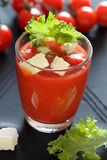 Glass of tomato juice with feta and salad. Ripe tomatoes, bloody mary in black background with salad Stock Images