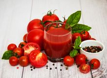 Glass with tomato juice. And fresh tomatoes on a table Stock Photography
