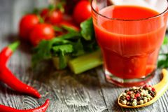 Glass of tomato juice with fresh tomatoes. Two glasses of tomato juice with fresh tomatoes and herbs on rustic wooden background. Selective focus Royalty Free Stock Photo