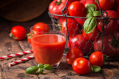 Glass of tomato juice. With fresh vegetables in a metal basket on rustic wooden background Stock Image