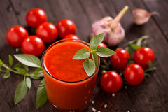 Glass of tomato juice on old wooden table Stock Photo
