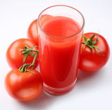 Glass of tomato juice and ripe tomatoes Stock Images