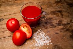 Glass with tomato juice and ripe tomatoes on a wooden table stock photography
