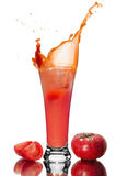 Glass of tomato juice. A slice of tomato drops in a glass of tomato juice, spray juice, fresh tomato Royalty Free Stock Photos