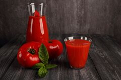 A glass of tomato juice and tomatoes with green basil leaves,. On a dark background
