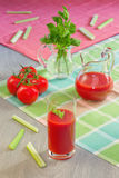 Glass with tomato juice, tomatoes, stalks and leaves of a celery on table. Glass with tomato juice, tomatoes, stalks and leaves of a celery on a table in style a Royalty Free Stock Photography