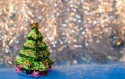 Glass toy Christmas tree on golden bokeh background. Stock Photo
