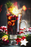 Glass of traditional mulled wine or punch with Christmas decoration , fir branches and festive bokeh. Lighting Royalty Free Stock Photos