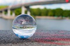 Glass transparent ball on bridge background and. Glass transparent ball on bridger background and grainy surface. Texture, outdoors Stock Photos