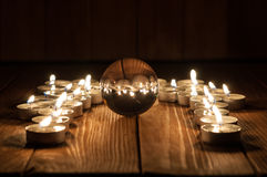Glass transparent ball and burning candles on old Royalty Free Stock Photos