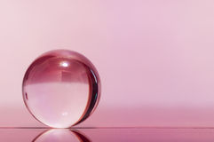 Glass transparent ball on light pink background and mirror surface. Royalty Free Stock Images