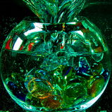 Glass transparent ball with maelstrom inside the water. Large glass transparent ball with  funnel from  maelstrom of water with air bubbles and colorful pieces Stock Photography