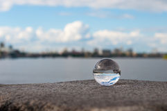 Glass transparent ball on river background and Stock Photo