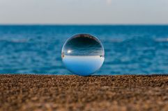 Glass transparent ball on sea background and Royalty Free Stock Photos