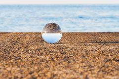 Glass transparent ball on sea background and Royalty Free Stock Photo