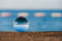 Glass transparent ball on sea background and Royalty Free Stock Photography