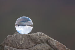 Glass transparent ball on the top of rock and dark Stock Photography