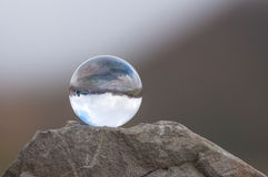 Glass transparent ball on the top of rock and dark Stock Photo