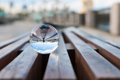 Glass transparent ball on wooden slats background Stock Images