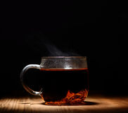 Glass transparent cup of hot tea on a black background Royalty Free Stock Image