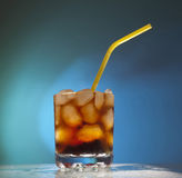 Glass transparent glass with ice. Cubes and Coke with a yellow tube Royalty Free Stock Photo