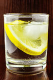 Glass of transparent purified water with slice of lemon and ice, on wooden table Stock Images