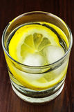 Glass of transparent purified water with slice of lemon and ice, on wooden table Royalty Free Stock Photo