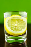Glass of transparent purified water with slice of lemon, on wooden table and blurred green background Stock Image