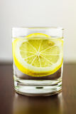 Glass of transparent purified water with slice of lemon, on wooden table, and blurred white background Stock Photography