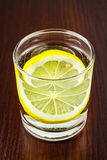 Glass of transparent purified water with slice of lemon, on wooden table Stock Photos