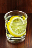 Glass of transparent purified water with slice of lemon, on wooden table Stock Photo